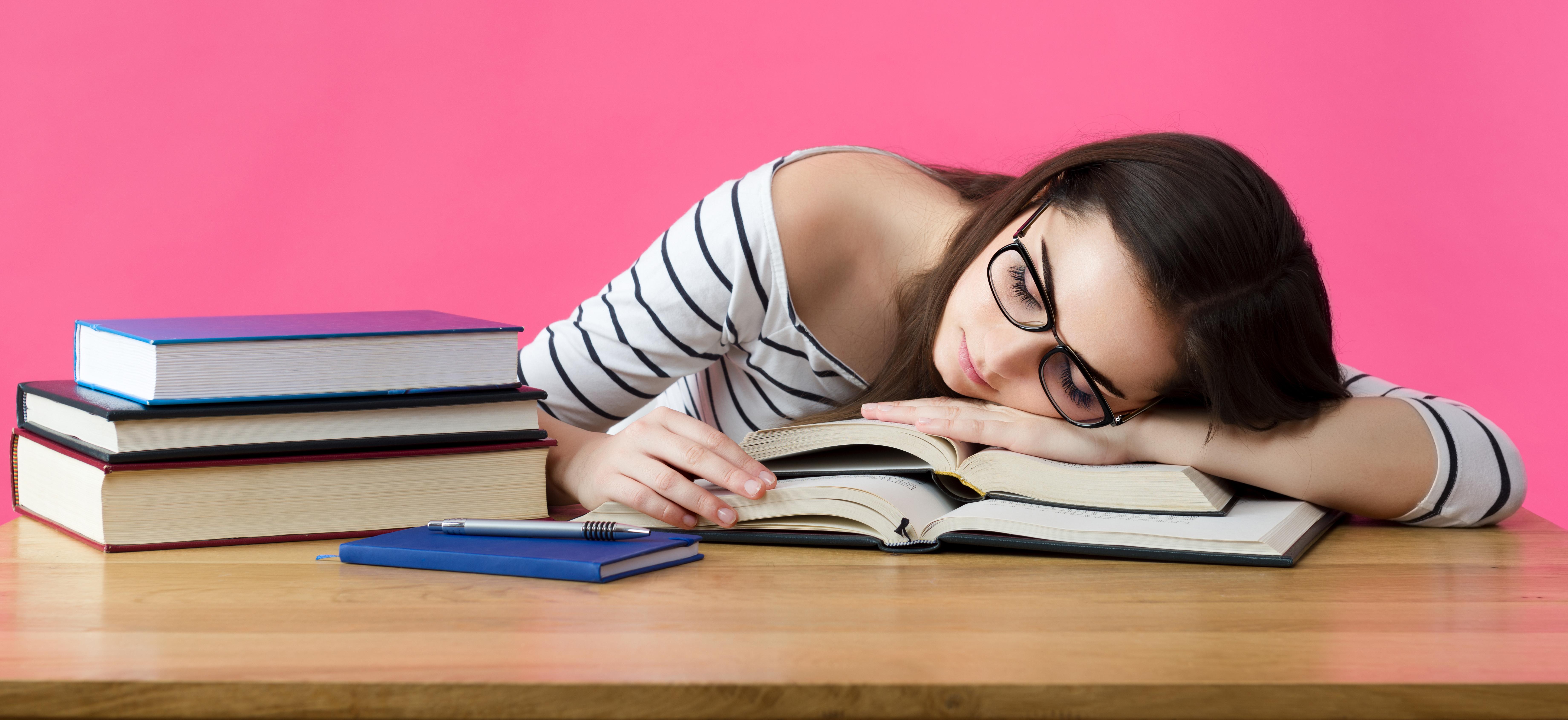Etudiante dormant sur des livres